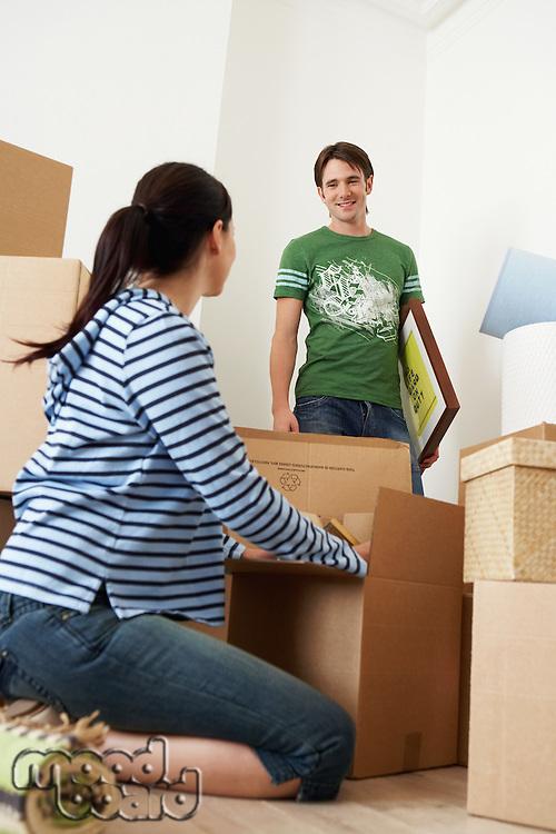 Woman unpacking box man looking