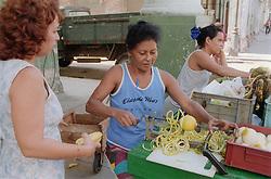 Woman using machine to peel lemon at street fruit stall in Havana; Cuba,