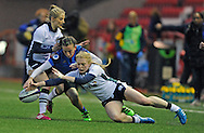 France's  Laura Delas  tackled by Scotland's Chloe Reilly and Megan Gaffney during the Women's Six Nations match between Scotland Women and France Women at Broadwood Stadium, Cumbernauld, Scotland on March 11th  2016.   AFP PHOTO / NEIL HANNA