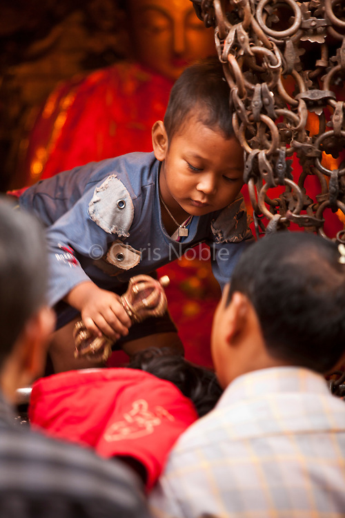 """A young boy dispense blessings with a """"dorje"""" symbol of enlightenment at Swayambunath, one of the oldest and most holy religious sites in Kathmandu."""