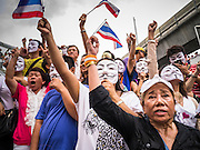 "02 JUNE 2013 - BANGKOK, THAILAND:  Anti-government protesters sing the King's Anthem during a protest against the incumbent government in Bangkok. The so called White Mask protesters are strong supporters of the Thai monarchy. About 300 people wearing the Guy Fawkes mask popularized by the movie ""V for Vendetta"" and Anonymous, the hackers' group, marched through central Bangkok Sunday demanding the resignation of Prime Minister Yingluck Shinawatra. They claim that Yingluck is acting as a puppet for her brother, former Prime Minister Thaksin Shinawatra, who was deposed by a military coup in 2006 and now lives in exile in Dubai.    PHOTO BY JACK KURTZ"