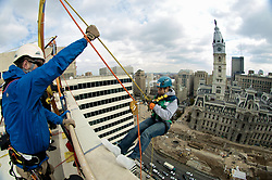 21 stories above ground level in Center City, Philadelphia, PA, USA - November 2, 2012; As they make the step over the edge rappellers have to overcome fair and rappel down more than 230ft.<br /> The participants first train at a one story instruction drop before heading for the big one.<br /> Philadelphia Mayor Michael Nutter is one of 'Fearless Rappellers'. Almost 70 attended the fundraising event, organized by Outward Bound Philadelphia and Over the Edge.