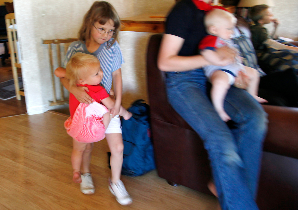 Hannah Jeub, 6 (L) carries her sister Priscilla past sister Lydia (R) holding brother Zechariah in the family home in Monument, Colorado July 17, 2009. Quiverfull believers Wendy and Chris Jeub have 15 children and would be happy to have more if God wills it they say. REUTERS/Rick Wilking (UNITED STATES)