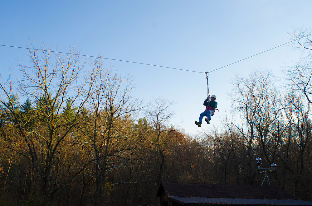 Bill Keuse of Kent, Ohio, zips down the zipline located at the Outdoor Pursuits challege course in the Ridges of Athens, Ohio. Keuse came to visit his daughter Ohio University's Dad's Weekend.