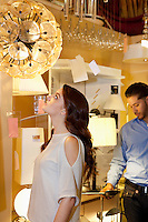Beautiful young woman looking at lighting fixture hanging while man browsing in background