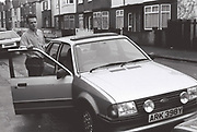 Peter McGowan standing with Ford Escort MK IV, Southall, UK, 1987.