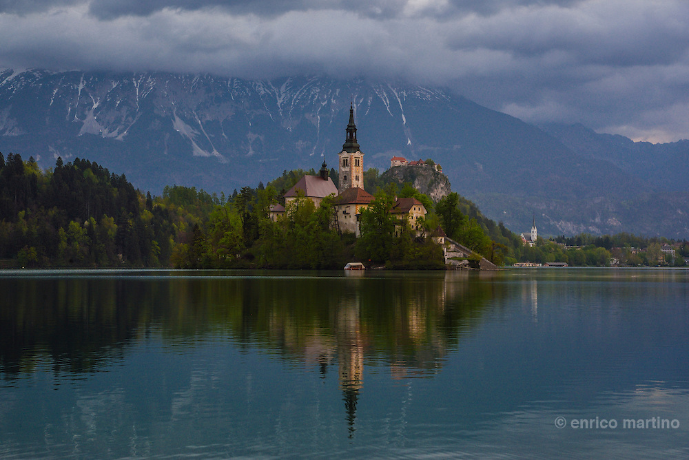 Sunrise view of the lake of Bled with the island and the Assumption's church. In the back the Bled castle.