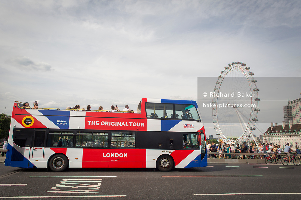 A tour bus with The Original Tour drives past the London Eye on Westminster Bridge, on 7th July 2017, in central London.