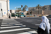 A Jewish man and Palestinian woman at opposite ends of a crosswalk, waiting to cross the street, in Jerusalem