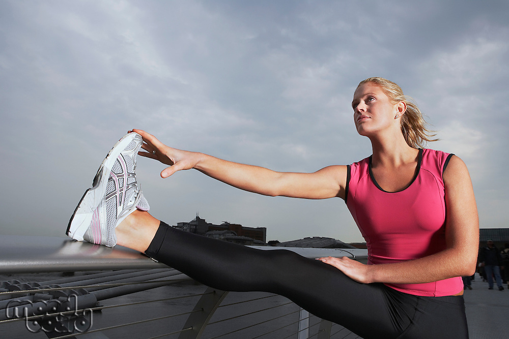 Woman stretching on foot bridge low angle view