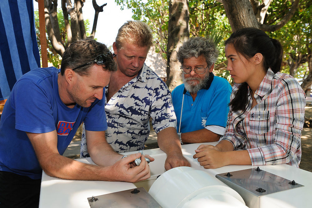 Sven Fautz (left to right) and Michael Cortenbach from Bali Diving Academy, Thomas Gereau from the Global Coral Reef Alliance and a student from Kuala Lumpur International School examining a Resen Wave generator, Pemuteran, Bali, Indonesia.