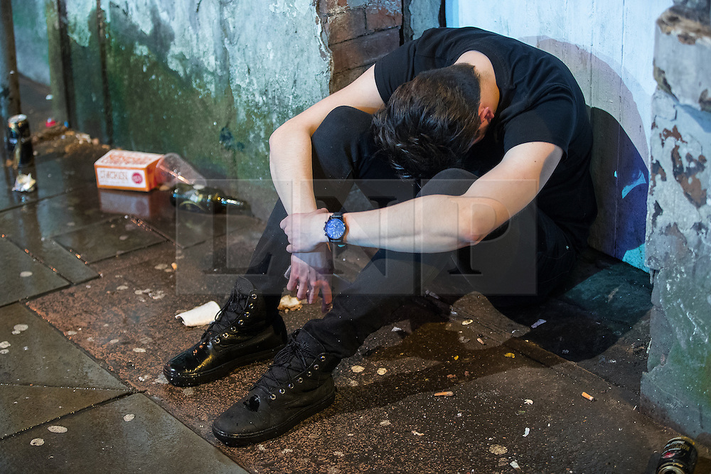 © Licensed to London News Pictures . 01/01/2017 . Manchester , UK . A man sits amongst litter on Dantzic Street . People on a night out in Manchester City Centre , after midnight on January 1st 2017 . Photo credit : Joel Goodman/LNP