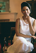black African American woman sitting in chair in white dress looking at the camera