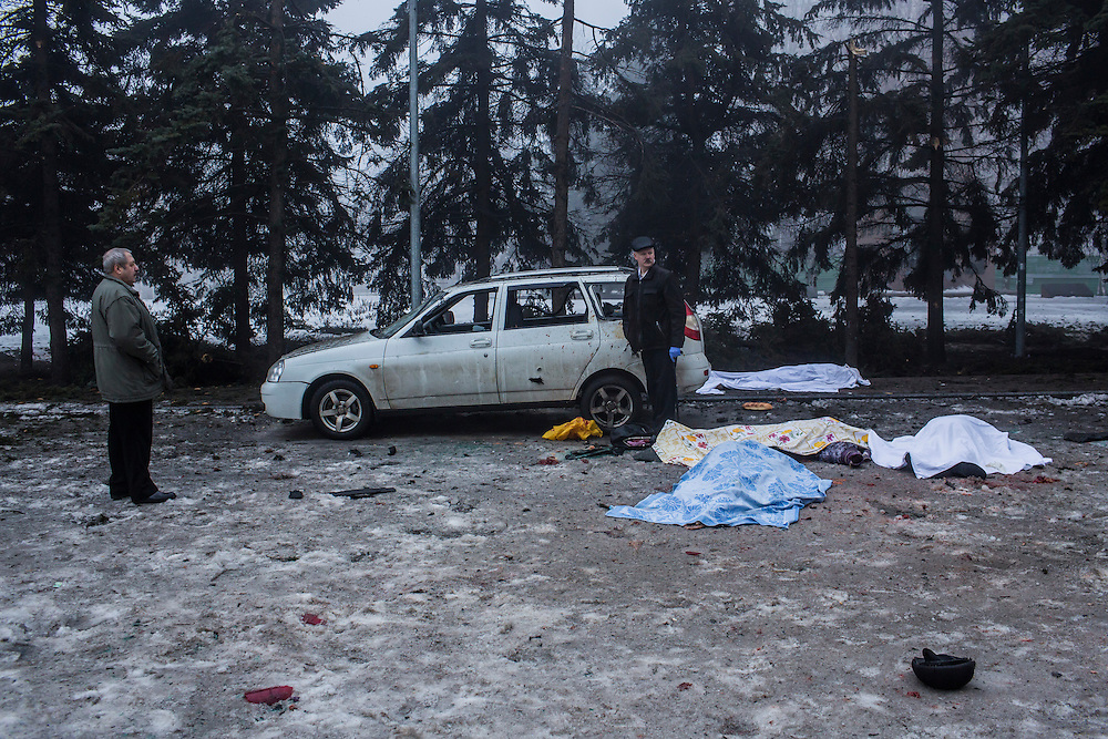 DONETSK, UKRAINE - JANUARY 30, 2015: Investigators examine the scene where a rocket struck the parking lot outside a center where humanitarian aid was being distributed, killing five people in Donetsk, Ukraine. At least two others died in a separate shelling nearby. CREDIT: Brendan Hoffman for The New York Times