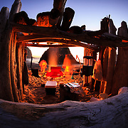 A camping group gathers wood and stokes their camp fire at sunset on Second Beach in Olympic National Park Washington.