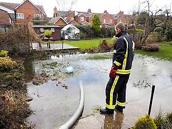 A fireman check out the pumping operation in a flooded garden in Marlow Thames Valley, United Kingdom. Tuesday, 18th February 2014. Picture by Max Nash / i-Images