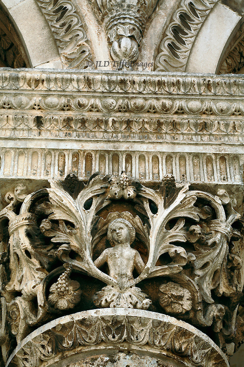 Intricate design of female figure, vines, dentils, and other ornamental rows, on a Romano-Byzantine column capital re-used in a later building..