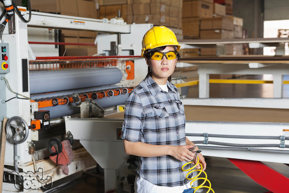 Portrait of an Asian female industrial worker with holding wire with machinery in background