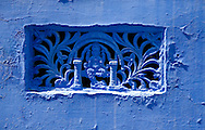 Intricate carved decoration on a traditional blue house in Jodhpur, Rajasthan, India