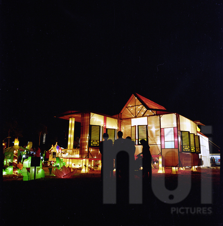 A vietnamese family stand in front of a lit up paper house illuminated at night in a street of Hoi An, Vietnam, Asia