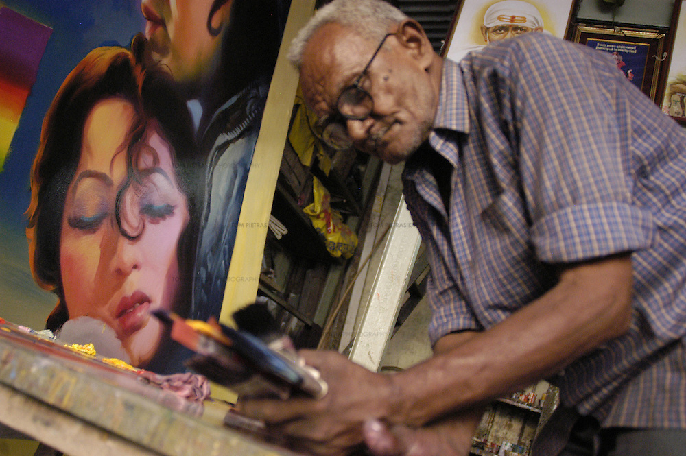 "An assistant clears up in front of a canvas for the film ""Mughal-E-Azam"" in the Ballakrinshna studio. ""Mughal-E-Azam"" was originally released in black and white in 1960. It has been re-released in 2004 having been ""coloured"" in post-production...Ballakrishna of Ballakrishna Art has been painting posters of Bollywood cinema stars for fifty years. Ballkrishna and his team of assistants produce paintings in a modest studio in central Bombay. With the advent of large, colour printing presses, Ballakrishna has been forced to diversify by painting posters for political rallies. He also paints canvasses for museums and private buyers in the West...Photo: Tom Pietrasik.Bombay, India .1.12.04...THIS PHOTOGRAPH IS THE COPYRIGHT OF TOM PIETRASIK. THE PHOTOGRAPH MAY NOT BE REPRODUCED IN ANY FORM OTHER THAN THAT FOR WHICH PERMISSION WAS GRANTED. THE PHOTOGRAPH MAY NOT BE STORED OR MANIPULATED WITHOUT PRIOR PERMISSION FROM TOM PIETRASIK...Tom Pietrasik.PHOTOGRAPHER.NEW DELHI.India tel: +91 9810614419.UK tel: +44 7710507916.Email: tom@tompietrasik.com.Website: tompietrasik.com"