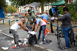 © Licensed to London News Pictures . 12/08/2018. Manchester , UK . Residents clean up rubbish on their street after police remove a cordon that has prevented road sweepers from doing the job on the second day of the annual Caribbean Carnival in Moss Side . A shooting on Claremont Road overnight lead to at least ten people being injured . Ten people are in hospital . Photo credit : Joel Goodman/LNP