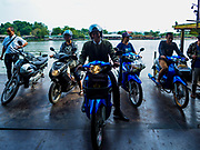 "09 JANUARY 2019 - KANCHANABURI, THAILAND:  Motorcyclists riding a ferry across the River Kwai leave the ferry it docked on the west side of the river. The ferry goes across the River Kwai downriver from downtown Kanchanaburi, the site of the famous ""Bridge on the River Kwai."" Small ferries like this, once common on Thai river crossings, are disappearing because Thailand has dramatically improved its infrastructure since this ferry started operating about 50 years ago. The ferry operator said his grandfather started the ferry, with a small raft he would pole across the river, in the late 1960s. Now his family has a metal boat with an inboard engine. There are large vehicle bridges across the river about 5 miles north and south of this ferry crossing, but for people in rural communities on the west side of the river the ferry is still the most convenient way to cross the river.     PHOTO BY JACK KURTZ"