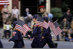 Americana Young cub and boy scouts march in small town holiday celebration parade.