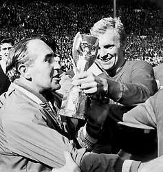Jubilant England captain Bobby Moore (r) shows the Jules Rimet trophy to manager Alf Ramsey (l) after their 4-2 extra time victory.
