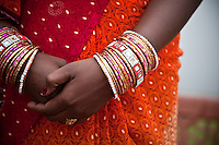 Woman's hands dressed with many gold bracelets near the Taj Majal