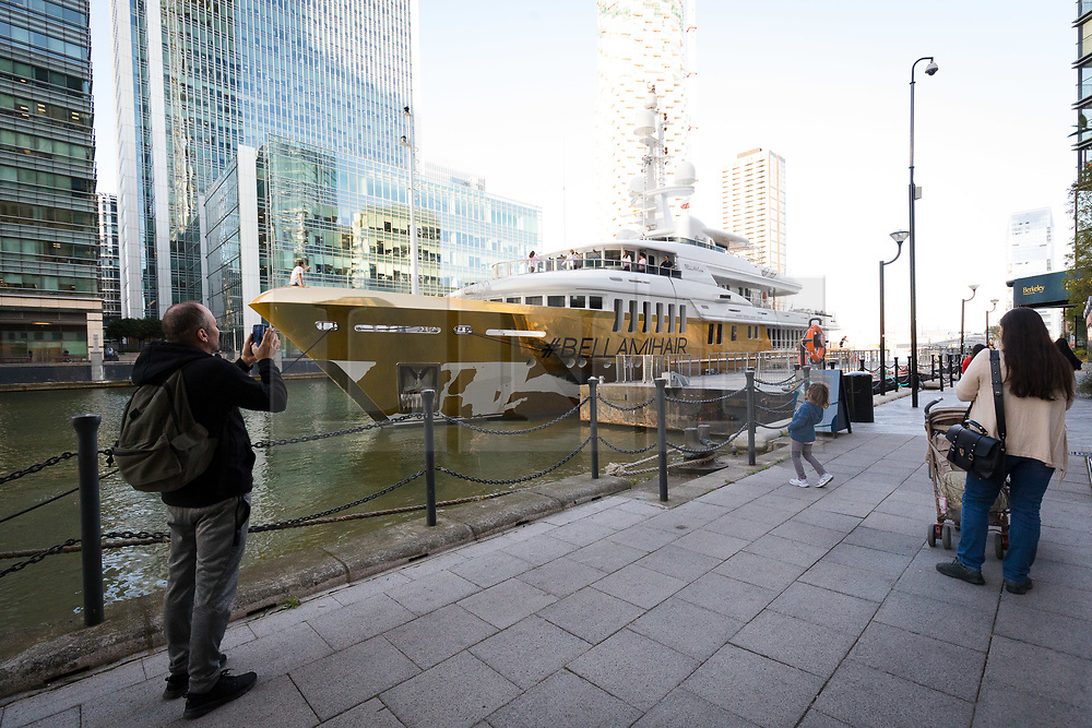 © Licensed to London News Pictures. 17/09/2019. London, UK. People look at gold wrapped, 175 feet long superyacht, Bellami.com which has moored in East India Dock. It took 13 days and 600sqm of gold chrome vinyl wrap to cover the superyacht formally known as 'Kinta' at the Port of Viareggio in Italy this year and is the largest chrome yacht wrap done fully in the water and possibly the largest chrome wrap ever. As Bellami.com arrived, it was noticed that some of the chrome wrap was already damaged and missing. Photo credit: Vickie Flores/LNP