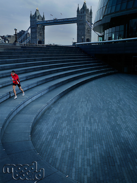 Male runner running along steps of the Scoop amphitheatre London England