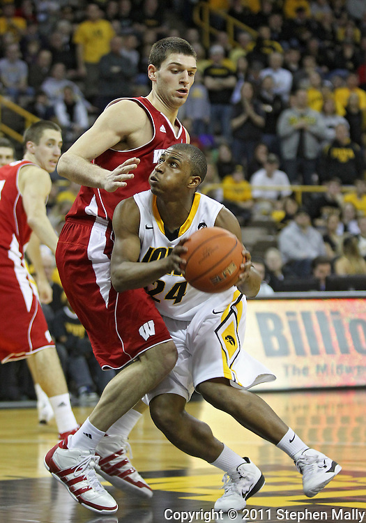 February 09 2011: Iowa Hawkeyes guard Bryce Cartwright (24) tries to get around Wisconsin Badgers forward Keaton Nankivil (52) during the second half of an NCAA college basketball game at Carver-Hawkeye Arena in Iowa City, Iowa on February 9, 2011. Wisconsin defeated Iowa 62-59.