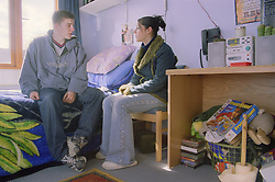 Young woman talking to her partner in bedsit at direct access hostel for homeless and vulnerably housed young people,