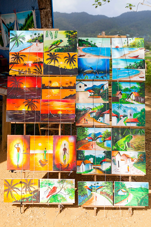 Outdoor display of art for sale painted by local artist in Mexico with mountains in the background.