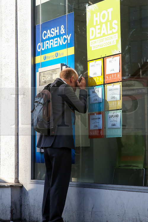 © Licensed to London News Pictures. 23/09/2019. London, UK. A man looks inside the branch of Thomas Cook in central London. The Civil Aviation Authority (CAA) announced shortly after 2 am this morning that the travel agent firm Thomas Cook hadceased trading with immediate effect. The liquidation puts 9,000 British jobs at risk and leaves the UK Government and CAA to fly home around 150,000 British holiday-makers left stranded around the world. Photo credit: Dinendra Haria/LNP