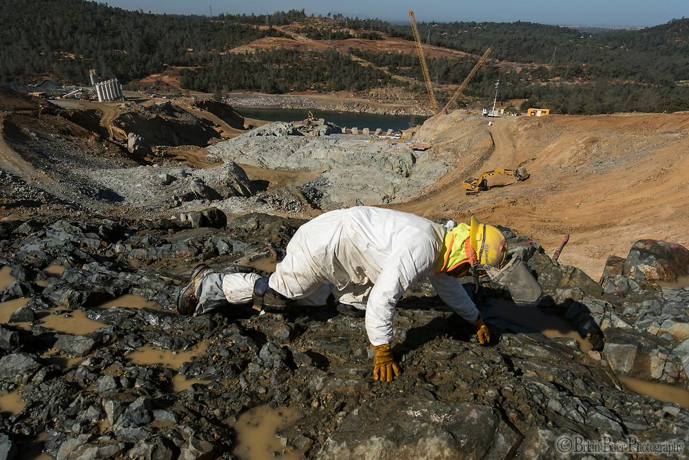 Workers on their hands and knees remove loose rocks and debris in preparation for concrete placement on the upper chute of the Lake Oroville flood control spillway in Butte County, California. Photo taken July 19, 2017. <br /> <br /> Brian Baer/ California Department of Water Resources<br /> FOR EDITORIAL USE ONLY