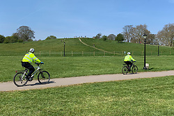 © Licensed to London News Pictures. 10/04/2020. London, UK. Police are seen cycling past people sunbathing (circled red) on Primrose Hill in London, during a pandemic outbreak of the Coronavirus COVID-19 disease. The public have been told they can only leave their homes when absolutely essential, in an attempt to fight the spread of coronavirus COVID-19 disease. Photo credit: Ben Cawthra/LNP