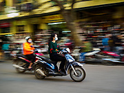 "21 DECEMBER 2017 - HANOI, VIETNAM:  Women drive motorcycles through the old quarter of Hanoi. The old quarter is the heart of Hanoi, with narrow streets and lots of small shops but it's being ""gentrified"" because of tourism and some of the shops are being turned into hotels and cafes for tourists and wealthy Vietnamese.  PHOTO BY JACK KURTZ"
