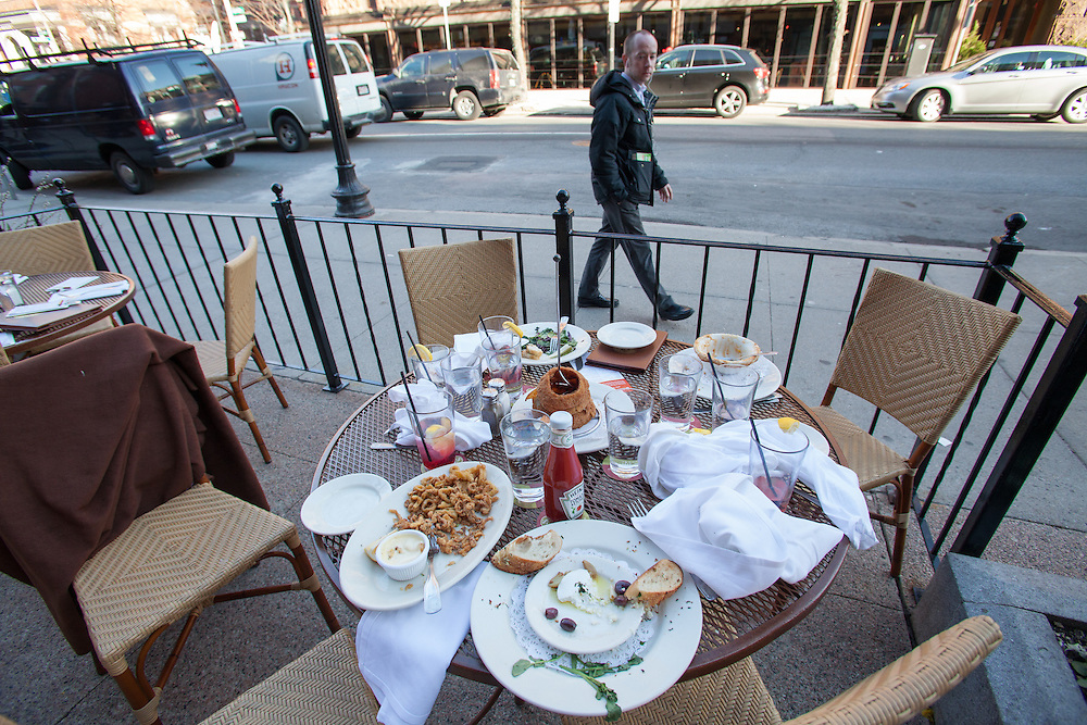 A pedestrian walks past abandoned tables at a sidewalk cafe on Newbury Street near the site of deadly twin bombings a day earlier, in Boston, Massachusetts, USA on 16 April 2013. At least three people died and more than a hundred were injured in an apparent terrorist attack in the northeastern US city.