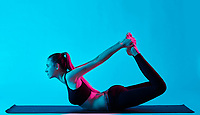 one caucasian woman exercising dhanurasana bow pose yoga exercices  in silhouette studio isolated on blue background