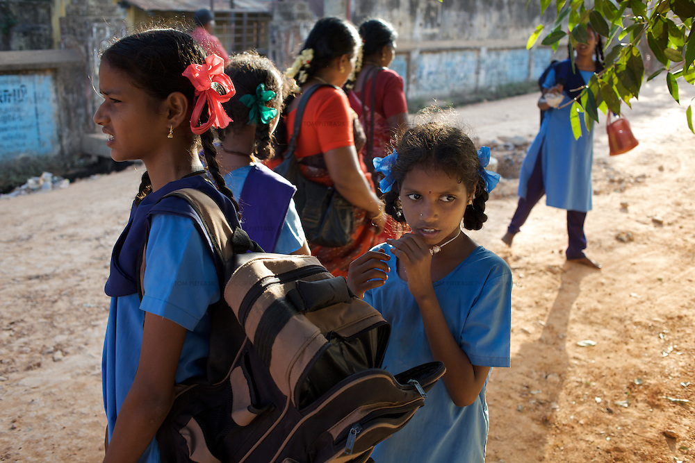 On a weekly visit, Krishnamurthy (not in photo) collects from school his three daughters attending Cuddalore's Government Girls High School. L to R foreground: Sivapriya (age 14). Anjalakshi (age 10)...The five Krishnamurthy sisters from Pudupettai were placed in the Government Home for Tsunami Children in Cuddalore, Tamil Nadu when they lost their mother to the 2004 tsunami. Their father, Krishnamurthy, had decided he could no longer provide day-to-day care for his daughters. Krishnamurthy later remarried. The Krishnamurthy sisters now range in age from eight to sixteen...The four younger sisters are still at the Governement home (or orphanage). In summer 2009, Sivaranjini, the eldest aged sixteen, failed her 10th Standard exams and had to drop out of school so leaving her not eligible for care at the Government home. She is now living with her father and his new wife Nagamalli's house 30km away in Pudupettai. Krishnamurthy is intending that Sivaranjini marry a second cousin in 2010. ..Krishnamurthy visits the Government orphanage once a week to see his four younger daughters. Nagamalli is popular with all five sisters. She provides them attention when they are together and is genuinely interested in their well-being. Sivapriya remains close to her paternal aunt Kamasala with whom she used to live in the fishing village of Thazanguda. Kamasala visits Sivapriya at the orphanage every fortnight. The sisters return to their father's home for festivals including Diwali and the Pudupettai village temple festival...According to Revathi, the staff member in charge at the Government home, the absence of the elder Sivaranjini has had the effect of making the remaining four sisters still at the home increasingly independent. For instance, where they used to all sleep together the girls now sleep in different dormitories. The eldest of these four, fourteen year-old Sivapriya has adopted some of the responsibilities of her elder sisters including coordinating clothes washing a