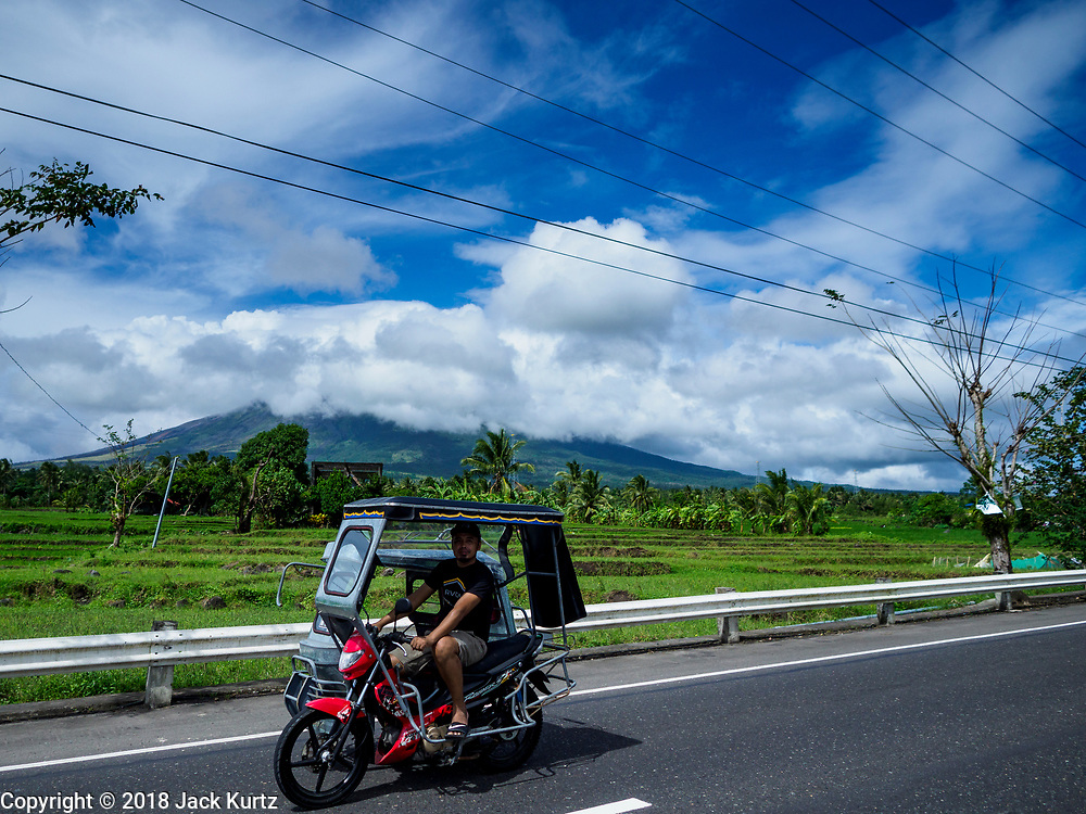 21 JANUARY 2018 - DARAGA, ALBAY, PHILIPPINES: A tricycle taxi passes the Mayon volcano, in the background, belching smoke and ash. Mayon volcano, the most active volcano in the Philippines.  More than 30,000 people have been evacuated from communities on the near the Mayon volcano in Albay province in the Philippines. Most of the evacuees are staying at schools in communities outside of the evacuation zone.    PHOTO BY JACK KURTZ