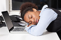 Side view of exhausted businesswoman with head on laptop in office