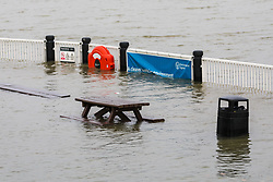 © Licensed to London News Pictures. 10/02/2020. London, UK. A bench and rubbish bin are seen underwater during flooding at the Thames Barrier in London which is seen closed this afternoon at high tide to protect the capital from flooding during Storm Ciara. The Thames Barrier prevents the floodplain of most of Greater London from being flooded by exceptionally high tides and storm surges.  Photo credit: Vickie Flores/LNP