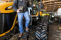 Farmer David Nelson steps down from the cab of his tractor carrying the iPad that he uses to plan and implement his corn and soybean  plantings on his farm near Fort Dodge, Iowa, on February, 18, 2014.