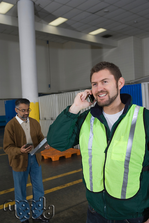 Man standing in factory using telephone