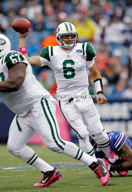 New York Jets quarterback Mark Sanchez (6) throws a pass while being tackled by the ankles during a NFL week 4 football game against the Buffalo Bills on Sunday, October 3, 2010 in Orchard Park, New York. The Jets won the game 38-14. (©Paul Anthony Spinelli)