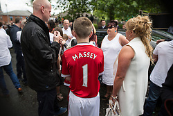 "© Licensed to London News Pictures . 28/08/2015 . Salford , UK . A boy wearing a Manchester United shirt with "" MASSEY 1 "" on the back , outside the church after the service . The funeral of Paul Massey at St Paul's CE Church in Salford . Massey , known as Salford's "" Mr Big "" , was shot dead at his home in Salford last month . Photo credit : Joel Goodman/LNP"