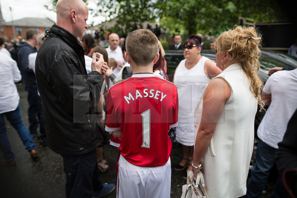 """© Licensed to London News Pictures . 28/08/2015 . Salford , UK . A boy wearing a Manchester United shirt with """" MASSEY 1 """" on the back , outside the church after the service . The funeral of Paul Massey at St Paul's CE Church in Salford . Massey , known as Salford's """" Mr Big """" , was shot dead at his home in Salford last month . Photo credit : Joel Goodman/LNP"""
